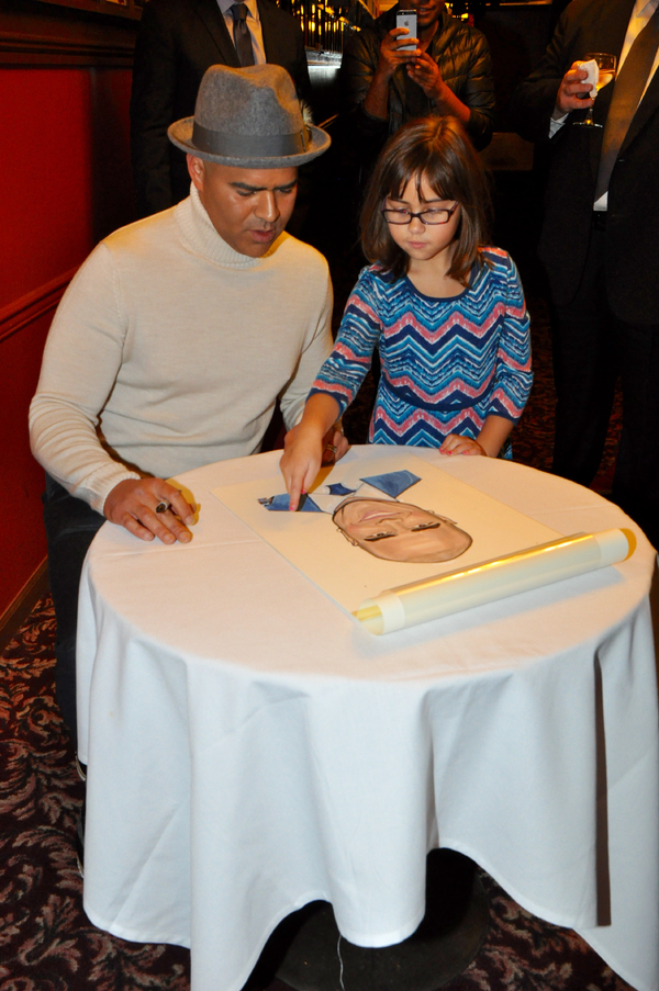 Daughter Jadelyn picks out spot for Christopher Jackson to sign his caricature
