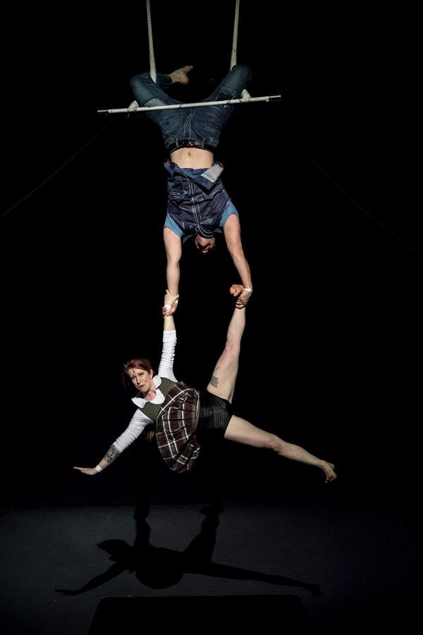 David Corlew holds Kate Braland in trapeze act