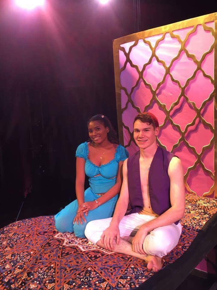 Photo of Alexis Dright (Jasmine), and Kaige Caswell (Aladdin) on the magic carpet