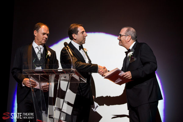 Principal Jeffrey Jones and Managing Director and Chief Operating Officer Craig Guiffre from American Benefits Consulting accept their award on stage at State Theatre New Jersey from State Theatre New Jersey President & CEO Tom Carto.