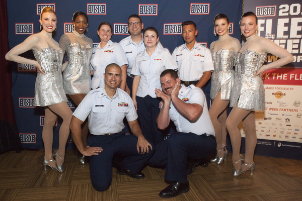 The Rockettes pose for a photo with service men.