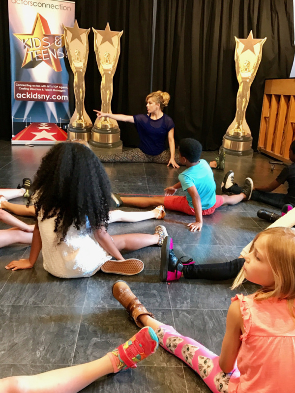 Kids group at Actors Connection Performing Arts Camp stretch with Felicia Finley before their musical acting lesson.