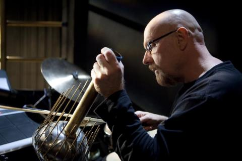 Musician Tom Teasley plays a percussive instrument