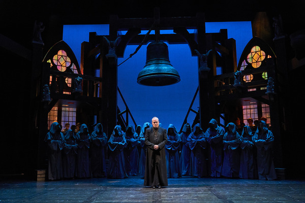 Dom Claude Frollo (Tom Ford*) is an imposing figure before his congregation with the ensemble: Derrick Cobey*, Aled Davies*, Jodi Dominick*, Jillian Kates*, Olivia Kaufmann, Andrew Kotzen*, Michelle Pauker, Mickey Patrick Ryan*, David Anthony Smith*, Nick