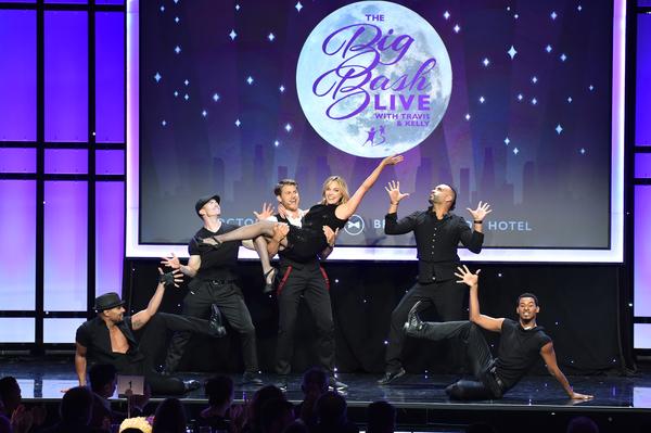 Travis Van Winkle holding Big Sister Kelly Sullivan (center) on stage with dancers