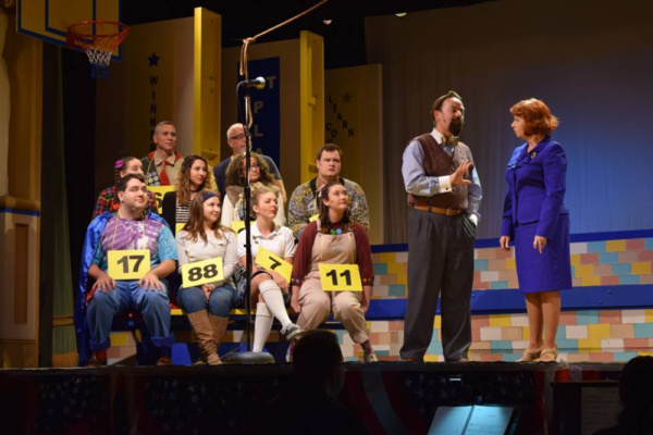 The 25th Annual Putnam County Spelling Bee cast and volunteers are led through the competition by the Bee's moderator, Rona Lisa Peretti (Chikita Wallace) and judge/word pronouncer Vice Principal Douglas Panch (Tim Koob)