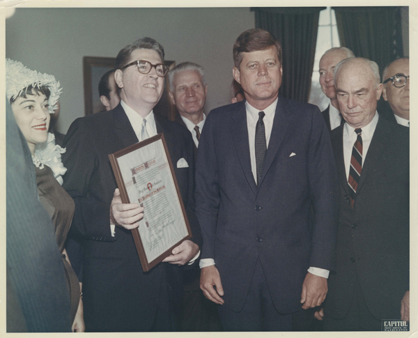 Meredith Willson and his second wife, Rini (left), receiving the Big Brother of the Year award from President John Kennedy in 1962.