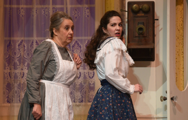 Rose (Lisa Schrock-Ohlinger) reacts to Katie (Mary Rumman) snooping on a telephone call from her beau in a scene from Meet Me in St. Louis at the Croswell.