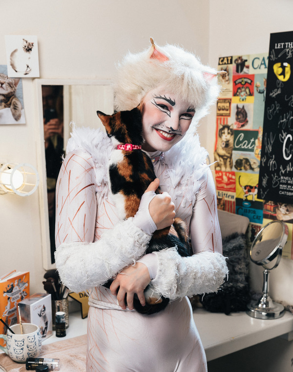 Claire Rathbun of the CATS cast shares a hug backstage with a shelter kitten