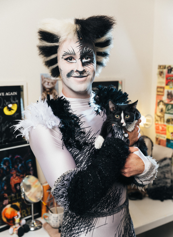 Sam Lips of the CATS cast poses alongside adoptable shelter cat from The Humane Society of New York shelter