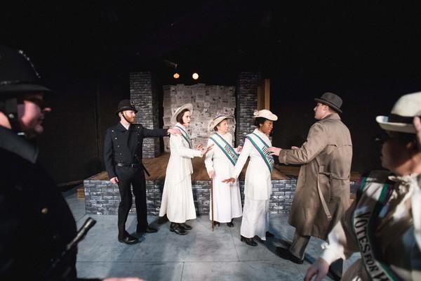 Grace Roe attempts to defend Emmeline Pankhurst from arrest. (L to R): Constable (Richard Traub), Constable (Joseff Stevenson), Gertrude (Scottie Caldwell), Mrs. Pankhurst (Jean Marie Koon), Grace Roe (Arielle Leverett), Inspector McBrien (David Kaplinsky