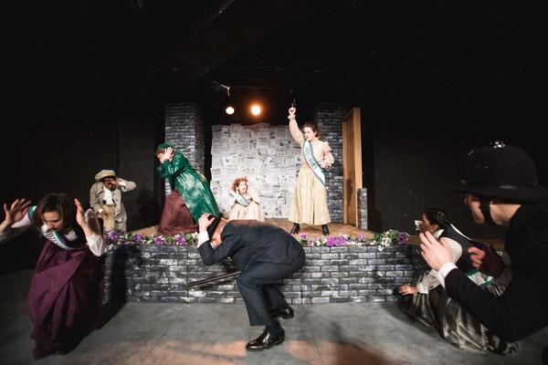 Hilda fires a gun to drive back the arresting officers at Emmeline Pankhurst's Glasgo Photo