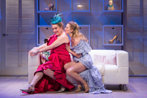 Mae (Eliza Huberth, right) encourages her Aunt Rene (Kristine Nielsen) to show off her $6,000 hat to party guests in Theresa Rebeck's comedy The Way of the World. On stage at Folger Theatre