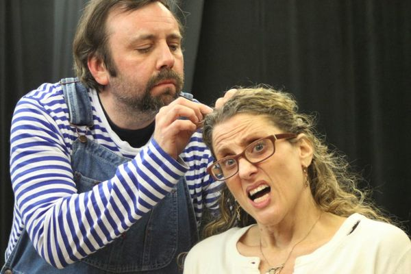 Eric Rupp, as Trevor the chimpanzee, treats his next-door neighbor, played by Jess Stinson, to a bit of grooming, in Trevor at the Players Club of Swarthmore.  Photo by Rose Azrael.