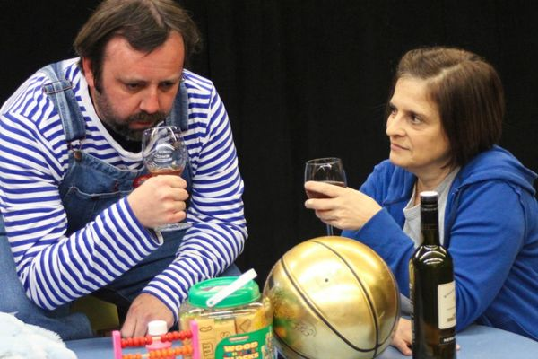 Eric Rupp, as Trevor the chimpanzee, evaluates the bouquet of his glass of wine while his housemate Sandra, played by Kathy Quinn, awaits his verdict, at the Players Club of Swarthmore.  Photo by Rose Azrael.