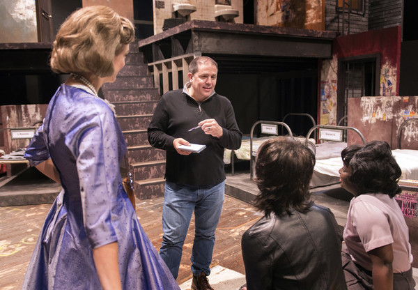 Director John Simpkins discusses notes with members of the cast of Love in a Hate Nation during rehearsal for the production.