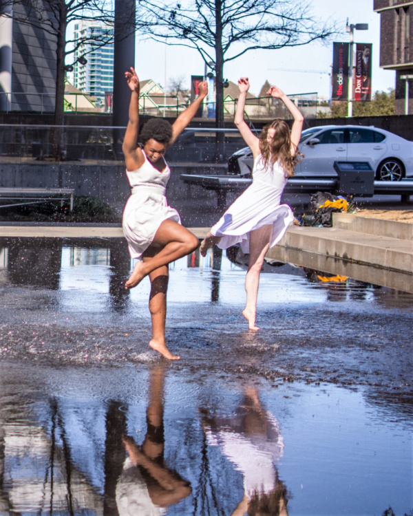 Dancers Ania Lyons and Mindy Neuendorff splash in the waters of the Donor Reflecting Pool at the AT&T Performing Arts Center.  Photo by Nathan Scott Photography