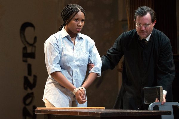 The Inquisitor (Eric Tucker) leads the accused Joan (Dria Brown) to her seat to stand Photo