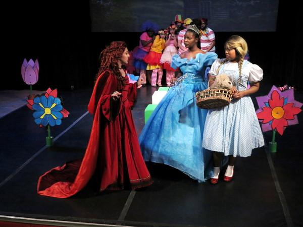 Emily Ramirez (Wicked Witch of the West), Barbyly Noel (Glenda), Taylor-Rey Rivera (Dorothy).  Behind:  Minchkin Ensemble.