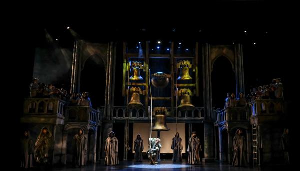 David  Burnham  (center)  as  Quasimodo  and  the  company. Photo