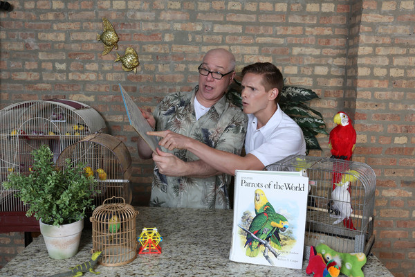 Chester Nurdiger (Ed Jones) shows Officer Frankie Spinelli (Chazie Bly) how to care for his new parrot in a publicity image for Hell in a Handbag Productions' comedy THE ARTIFICIAL JUNGLE.