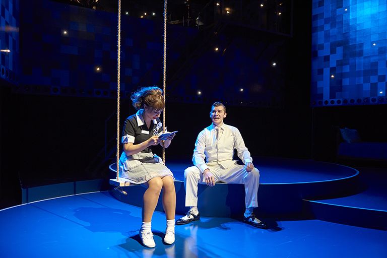A production still from a performance of Fly by Night. A young woman with bangs and hair pulled back in a large ponytail sits on a swing with a book. A man in a white suit sits nearby.