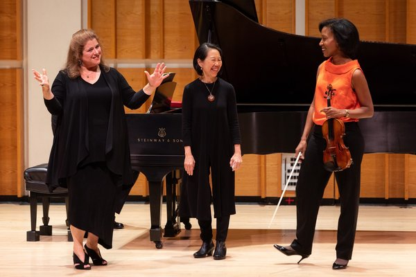 Allison Charney with violinist Kelly Hall-Tompkins and pianist Donna Weng Friedman discussing the challenges of interpreting a new work.