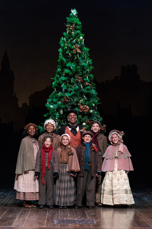 Craig Wallace as Ebenezer Scrooge and the young cast of the 2018 Ford's Theatre production of A Christmas Caro