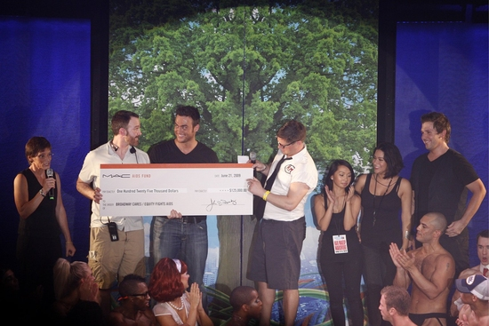 Nancy Mahon from MAC AIDS Fund and BC/EFA's Michael Graziano present a check to Cheyenne Jackson and Christopher Seiber