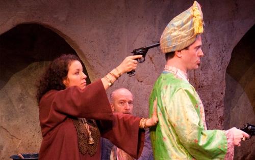 Ambara (Suehyla El-Attar) holds British Lieutenant Douglas Duff (Joe Knezevich) at gun point as Hajj Waleed (Tom Thon, background) watches.