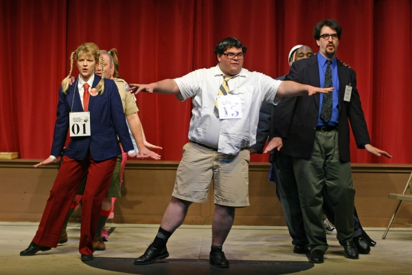 (l to r) Vicki Sosbe as Logainne Schwarzandgrubenierre, David Anctil as William Barfee,        and Michael Wright as Vice Principal Panch (all front row)