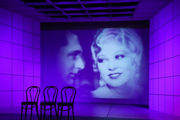 A scene from 'Dirty Blonde' featuring a photo of Cary Grant and Mae West from the Paramount film 'I'm No Angel.' at 6th Street Playhouse Presents DIRTY BLONDE