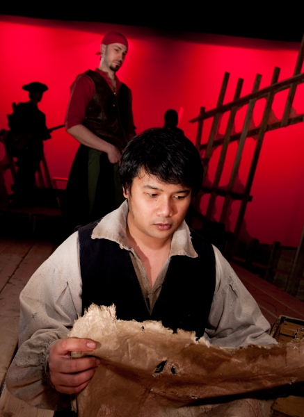 Kroydell Galima as Jim Hawkins (foreground) and James Anthony Zoccoli as Long John Silver (background)