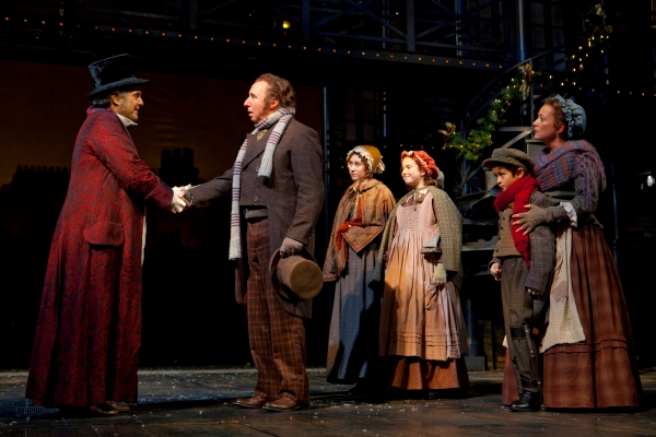 Edward Gero as Ebenezer Scrooge and Christopher Bloch as Bob Cratchit, with (background) Brooke Bloomquist as Martha Cratchit, Caleigh Davis as Belinda Cratchit, Stephen Scholl as Tiny Tim and Amy McWilliam