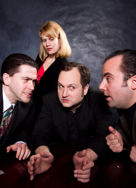 (left to right) The Commissioner (Eric Paskey), the Madman (Joseph Stearns), and Sporty (Anthony Tournis) conspire together while the Reporter (Simone Roos) listens in