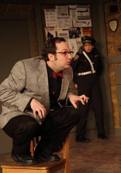 The Madman (Joseph Stearns, left) shocks Officer #1 (Elizabeth Bagby, right) with his strange behavior