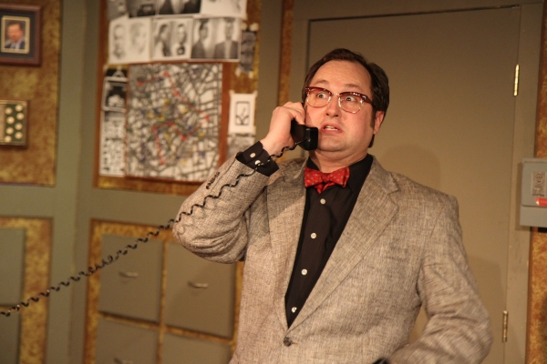 The Madman (Joseph Stearns) impersonates a police officer on the phone Photo