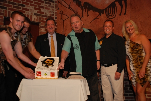 Caveman assistants, Harrah's President Rick Mazer, and Caveman producer John Bentham with the celebratory cake