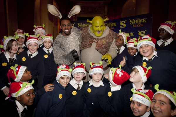 Richard Blackwood (Donkey) and Nigel Lindsay (Shrek) backstage with students from Blessed Sacrament RC Primary School backstage at Shrek The Musical at the Theatre Royal Drury Lane, London, England on 15th December 2011