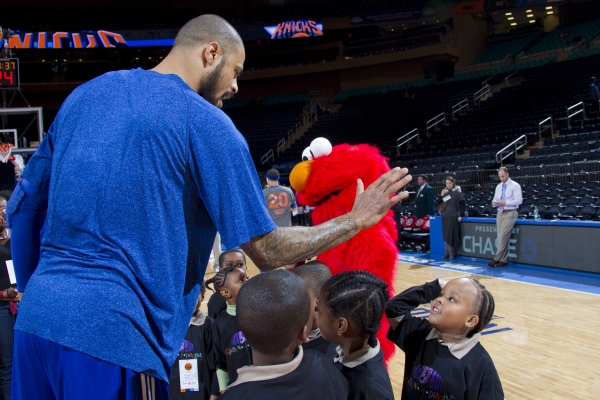 Elmo and New York Knick Tyson Chandler give high fives to children from the Garden of Dreams Foundation