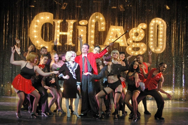 Alexis Grace,(center left) as Roxie Hart and Rob Hanford (center right) as Billy Flynn in the Theatre Memphis production of Chicago, March 9 – April 1, 2012. They are surrounded by the company chorus.
