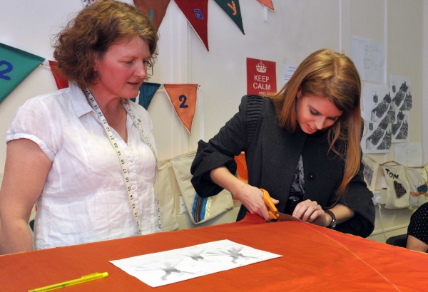 Steady as she goes. HRH Princess Beatrice tries her hand at pattern cutting as she scissors her way through material for an angel cosdtume at the York Mystery Plays' costume workshop in York during a private visit. Watching HRH is community wardrobe super